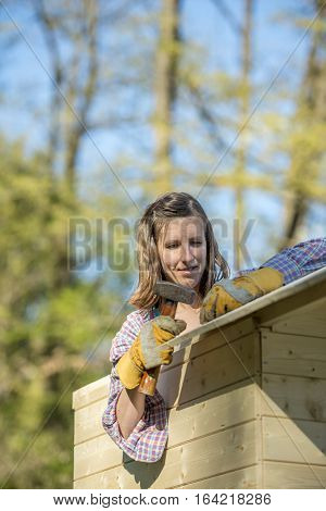 DIY concept - young woman holding a hammer working on a wooden playhouse wearing protective gloves outside in backyard.