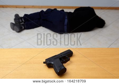 Dead man lying on the floor and a pistol standing on the table.Murder or suicide.