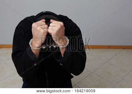 Closeup view of handcuffed man hidding his face.