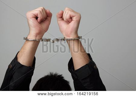 Closeup view of handcuffed man rising his hands.