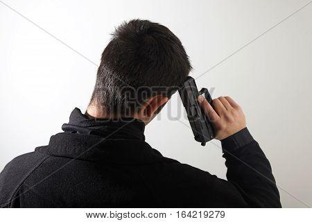 Young man suiciding with pistol a gun.