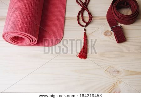 Pink yoga mat with red mala bead necklace and belt onwooden background. Yogi Essentials for practice and meditation.Copy space