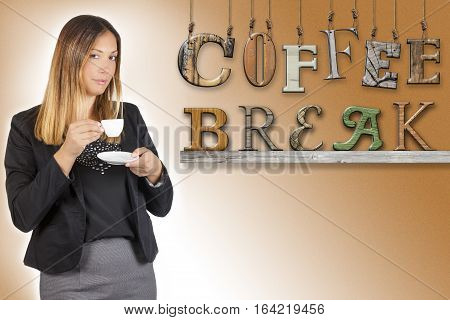 Business woman drinking coffee. Coffee break text word. Work pause. A woman is standing having a coffee during her coffee break. Next to her, on brown gradient background, the word coffee break hanging and on the wooden shelf