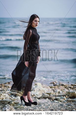 Beautiful sad gothic woman in black dress standing on the sea beach