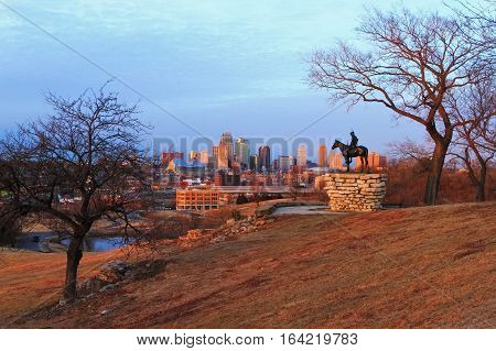 View of Kansas City Missouri skyline at dusk during golden light from the Kansas City Scout Memorial with all registered trademarks removed.