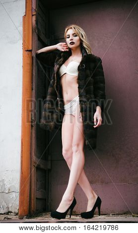 Beautiful sexy young woman in fur coat and underclothes. Full length