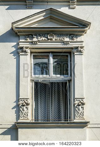 Open window decorated with bas-relief old gray building in Lviv (Lvov) Ukraine