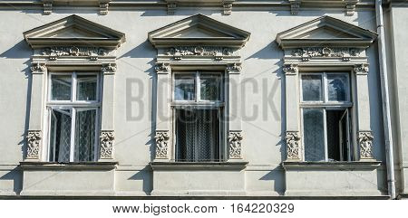 Three open windows decorated with bas-relief old gray building in Lviv (Lvov) Ukraine