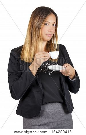 Business woman drinking coffee in cup. Work pause. A standing woman having a coffee during her coffee break. The beautiful young woman is drinking holding a small white cup of coffee.