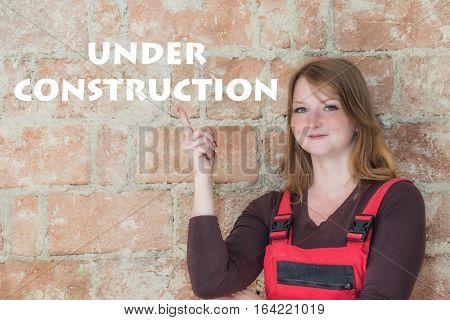 Attractive young redhead woman is standing in front of an old brick wall. Woman is looking at the camera and is pointing the finger at the sign Under Construction.