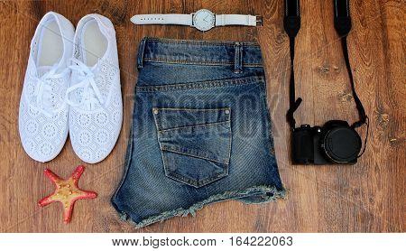 Set clothes for going to sea: jeans shorts, sneakers, watches, photocamera, shells, a top view of wooden background.