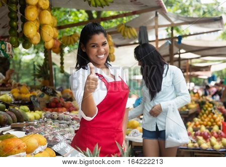 Laughing mexican saleswoman showing thumb up on a farmers market in latin america