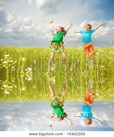 Two golden-haired children playin the field. Specular reflection in water