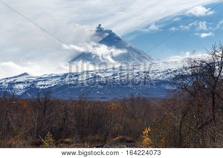 Volcanic landscape of Kamchatka: active Klyuchevskoy Volcano view of volcanic eruption - plume of gas steam and ash from crater. Kamchatka Peninsula Russian Far East Klyuchevskaya Group of Volcanoes.