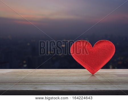 Fabric red love heart on wooden table over blur aerial view of cityscape on warm light sundown Valentines day concept
