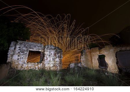Light painting in abandon house with spinning steel wool making fire