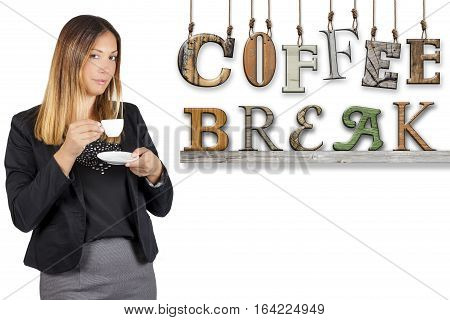 Coffee break text word business woman drinking coffee. Work pause. A woman is standing having a coffee during her coffee break. Next to her, on white background, the word coffee break