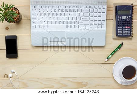 Top view notebook pencil black coffee cactus watch Laptop stationary pen calculator on office desk background.