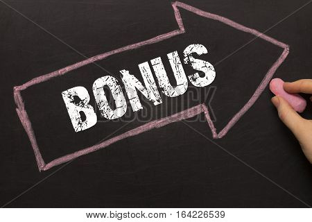 Bonus Arrow With Text On Chalkboard Background With Female Hand