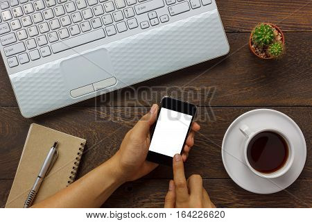 Top view business man using mobile phone and coffee laptop notebook cactus on wooden office desk.