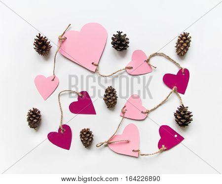 Bright pink paper hearts connected with a rope. Cards for Valentine's day decorated with cones. Flat lay on white background with place for text top view