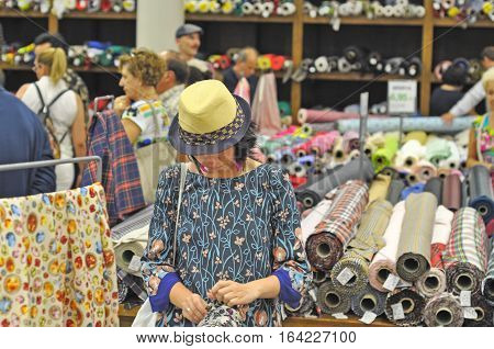 SPAIN BARCELONA - SEPTEMBER 2016: young girl female in a hat looking for fabric in the tissue store rolls of textile fabric on background