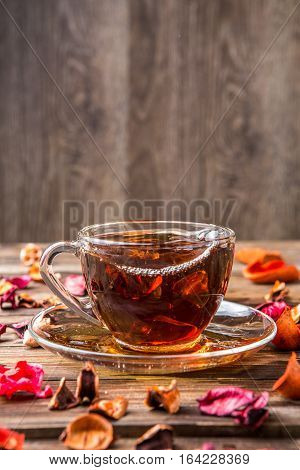 Photography of teacup on table with petals on wooden background
