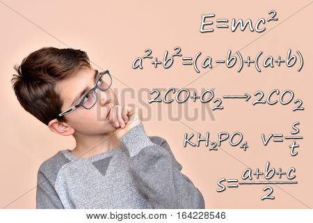 Thoughtful cute schoolboy with glasses thinking about mathematics, physics and chemistry formulas