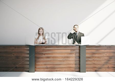 Attractive young businesspeople at wooden reception desk in interior. 3D Rendering