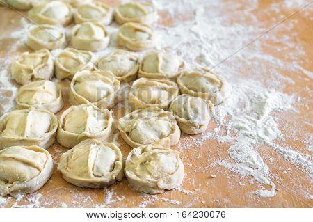 Homemade manti (dumplings) on kitchen board with flour.
