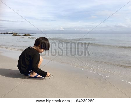 4 years old black hair Asian boy sand writing lonely on beach with sea and sky background and copy space