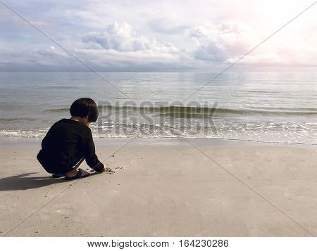4 years old black hair Asian boy sand writing lonely on beach with sea and sky background with flare and copy space