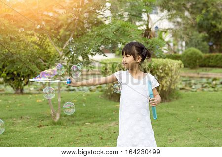 7 years old black hair Asian girl in white dress play and enjoy with soap bubbles balloon in park with flare and vintage tone