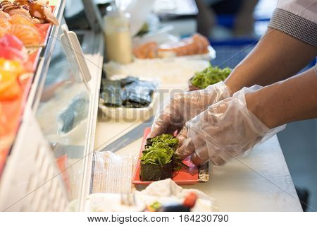 chef hand in glove cooking seaweed maki roll japanese food on tray