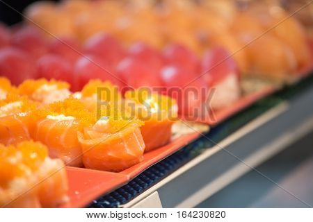 row of group of salmon maki roll sushi with copy space