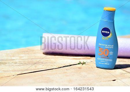 Bottle Of Brazilian Nivea Sunscreen In Front Of A Pool