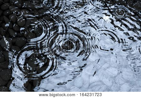 Raindrops on the water surface and pebble stones