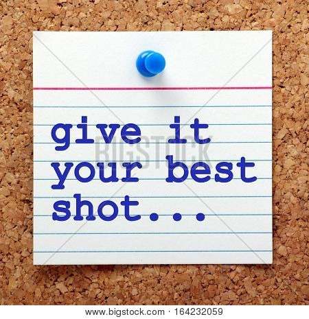 The words Give It Your Best Shot on a note card pinned to a cork notice board as a reminder to put in your best effort to achieve success