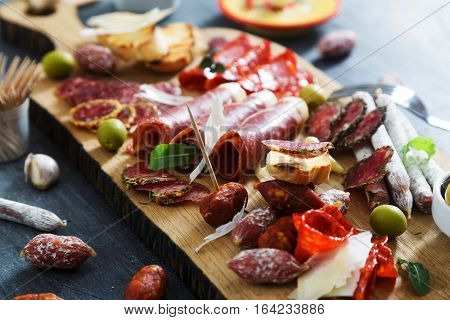 Cured meat platter of traditional Spanish tapas - chorizo, salsichon, jamon serrano, lomo - erved on wooden board with olives and bread.