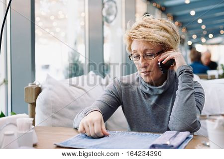Mid age womantalking on cell phone sitting at indoor cafe looking for screen