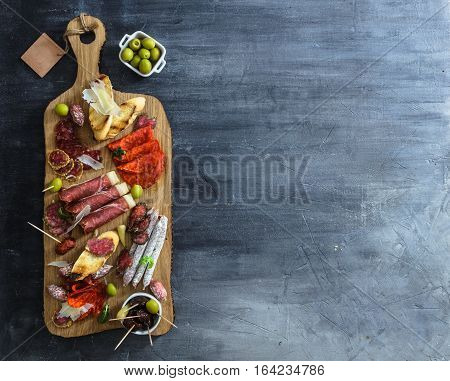 Typical spanish tapas concept. Concept include variety slices jamon, chorizo, salami, bowls with olives, peppers, anchovies, spicy potatoes, mashed chickpeas on a wooden table. Copyspace.