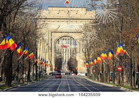 The Arch Of Triumph (arcul De Triumf) From Bucharest Romania, National Day With Romanian Flags, View