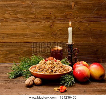 Plate with traditional Christmas treat Slavs on Christmas Eve. Compote spruce branch apples and candle on a wooden background. Space for text