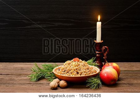 Traditional Christmas treat on Christmas Eve Slavs kutia on a black background. Fur-tree branch apple candle on a wooden background. Space for text