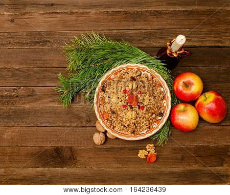Top view of a dish of traditional Christmas dish Slavs - kutia. Wooden background spruce branch apples. Space for text