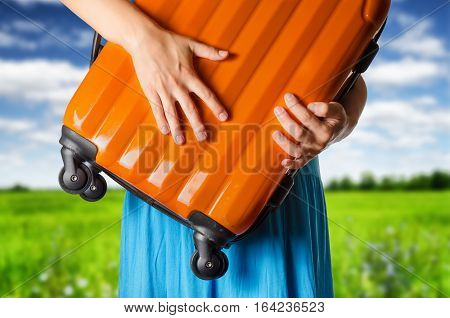 Woman In Blue Dress Holds Orange Suitcase In Hands On The Field Background