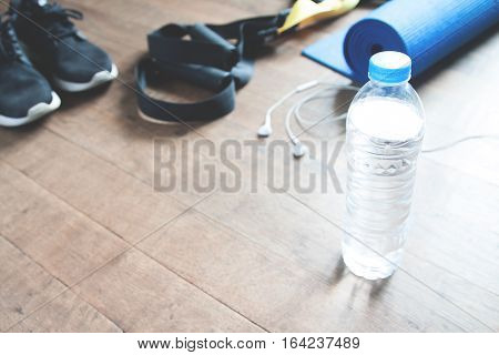 Fitness concept with bottle of water sneakers TRX yoga mat and earphones on wood floor Copy space