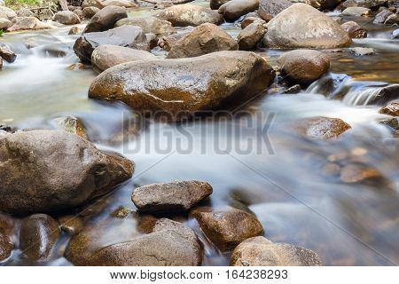 Natural rocks over the flowing clear water.