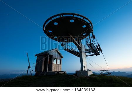 A lonesome ski lift and building under a summer starry sky at Mt Buller in the Victorian High Country, Australia