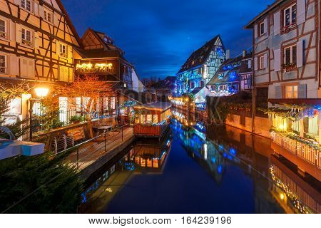 Traditional Alsatian half-timbered houses and river Lauch in Petite Venise or little Venice, old town of Colmar, decorated and illuminated at christmas time, Alsace, France